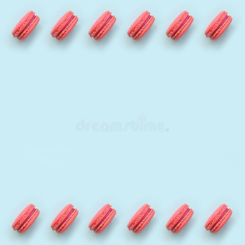 桃红色点心蛋糕macaron或蛋白杏仁饼干在时髦淡色蓝色背景顶视图 平的被放置的样式构成 免版税库存图片