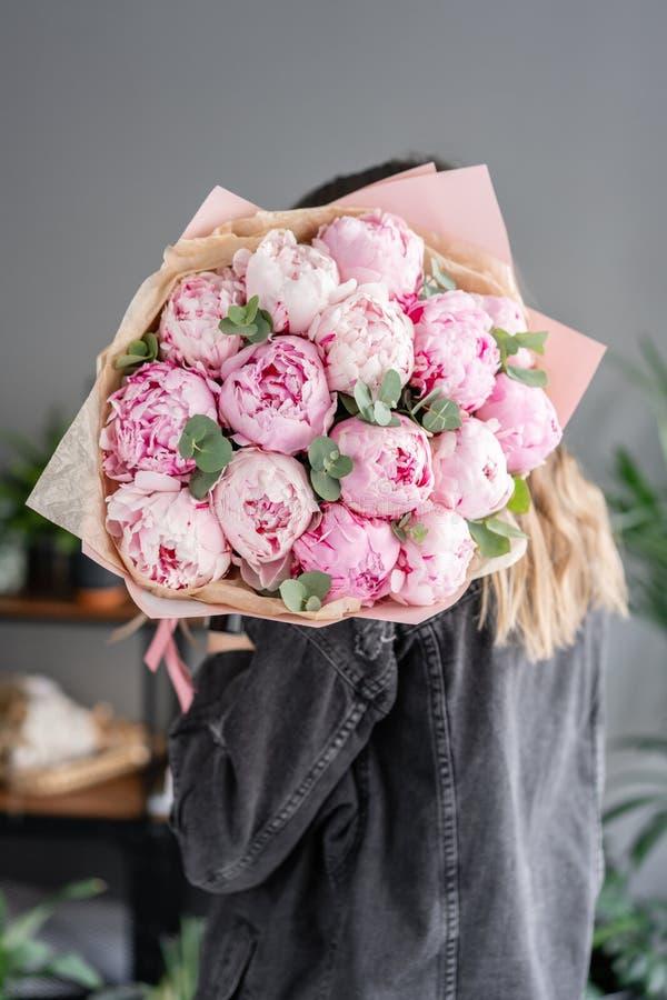桃红色牡丹在妇女手上 编目或网络商店的美丽的牡丹花 花卉商店概念 美丽新鲜 库存照片
