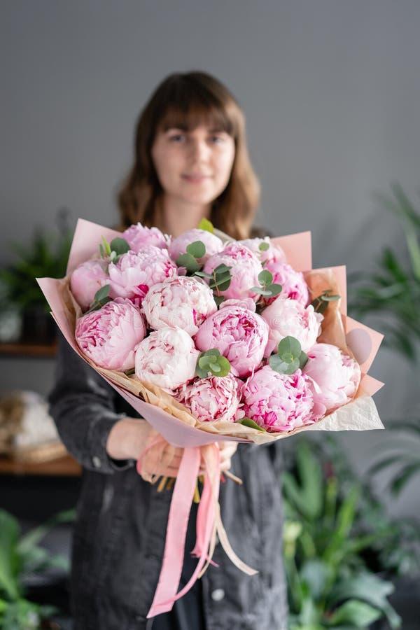 桃红色牡丹在妇女手上 编目或网络商店的美丽的牡丹花 花卉商店概念 E 免版税库存图片