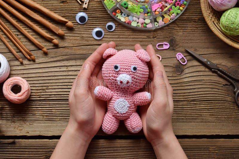 桃红色猪 钩编编织物孩子的玩具 在桌上穿线,针,勾子,棉纱品 制作手工制造 diy的概念 3d商业查出的小的白色 库存照片