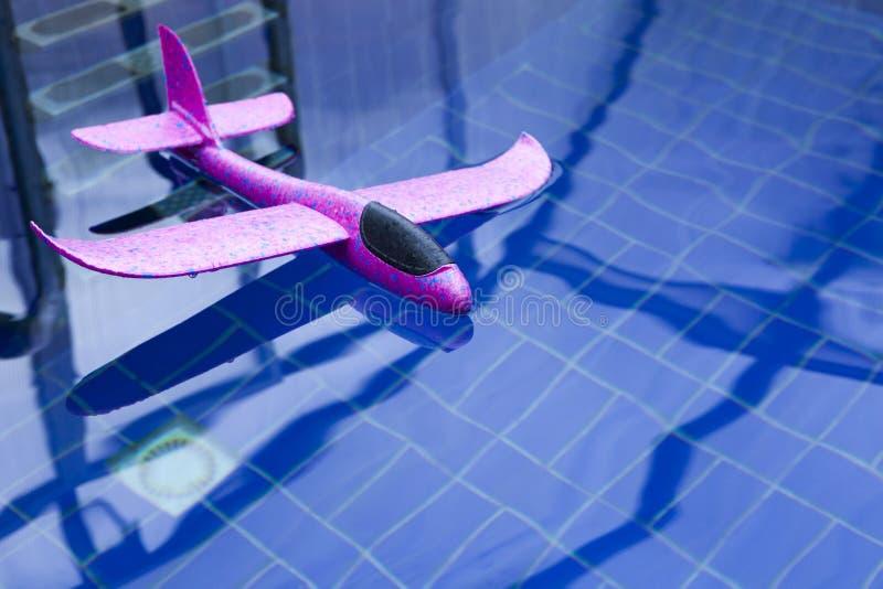 桃红色玩具飞机游泳场没人 库存照片