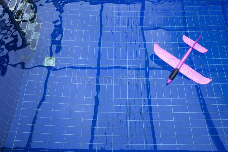 桃红色玩具飞机游泳场没人 库存图片
