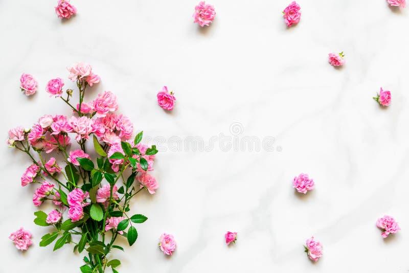 桃红色玫瑰开花与框架的花束由有拷贝空间的花蕾制成在白色大理石桌 平的位置 顶视图 免版税库存照片