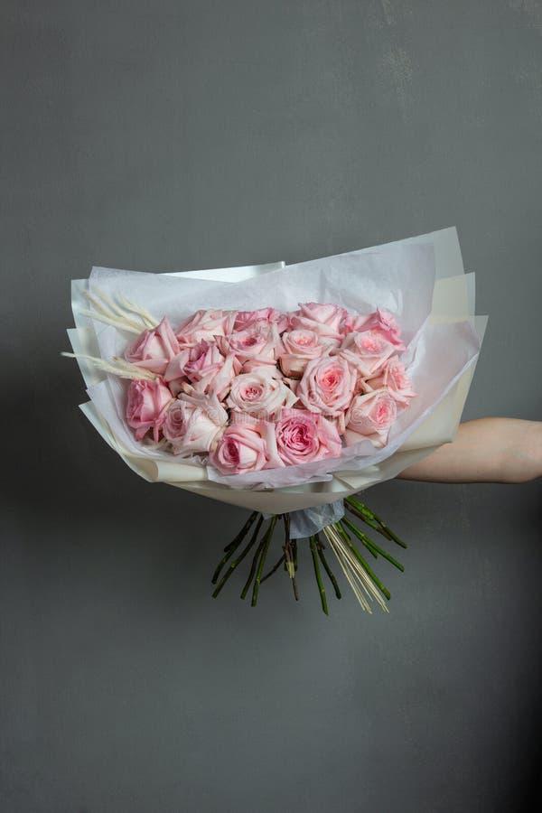 桃红色玫瑰时髦花束在被伸出的手上在灰色背景 免版税库存图片