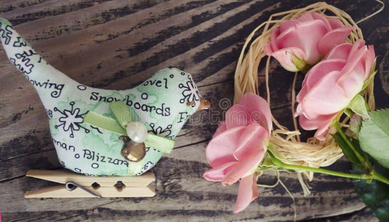 桃红色玫瑰的图象在老棕色木背景的巢和鸟玩具开花 顶视图 春天装饰鸟 装饰玩具o 库存照片