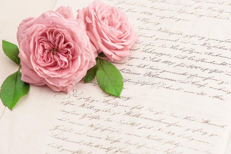 桃红色玫瑰花和老手写的信件 库存图片