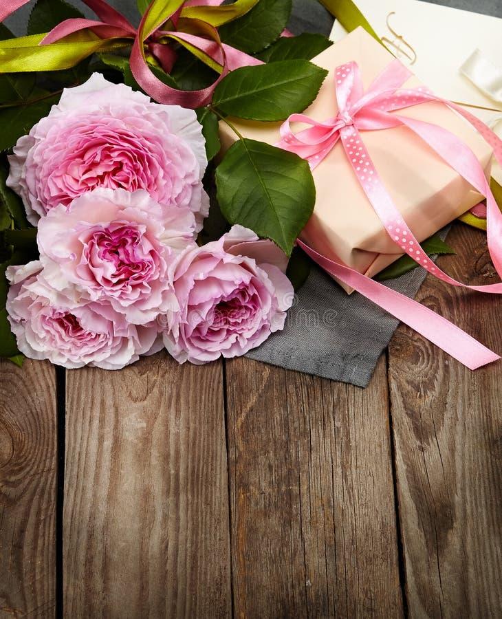 桃红色玫瑰花束和礼物盒在木背景 免版税库存照片