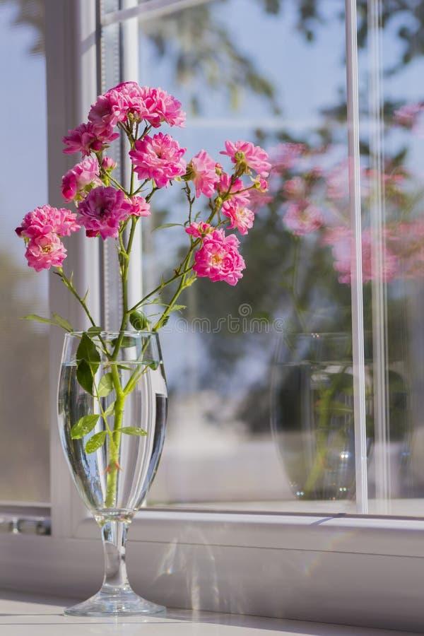 桃红色玫瑰花束在玻璃近的窗口里 图库摄影