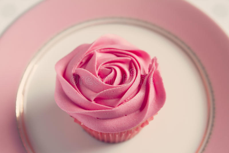桃红色玫瑰结霜的杯形蛋糕顶上的细节  库存照片