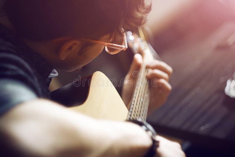 桃红色玻璃的一个人播放在一把声学吉他的一支曲调 免版税库存图片