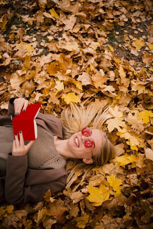 桃红色玻璃谎言的美丽的年轻金发碧眼的女人在黄色秋叶,读在红色盖子的一本书 免版税库存图片