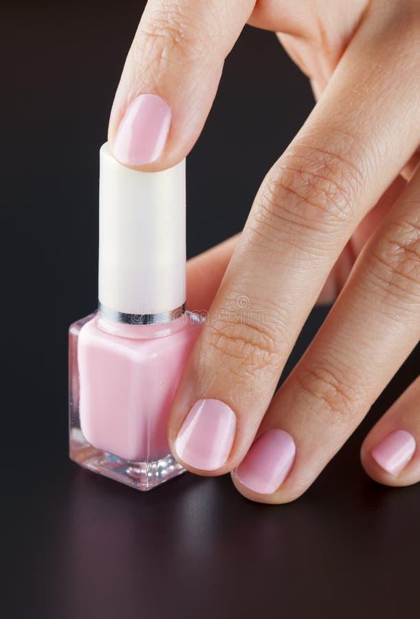 桃红色瓶在妇女手上指甲油 免版税库存照片