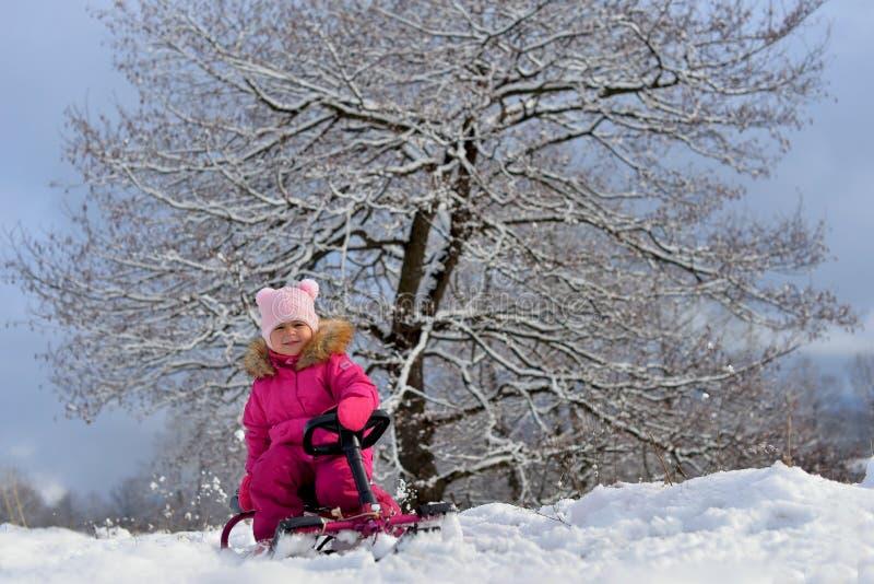 桃红色的一女孩在夹克下坐雪撬在一棵树下在多雪的冬天 库存照片