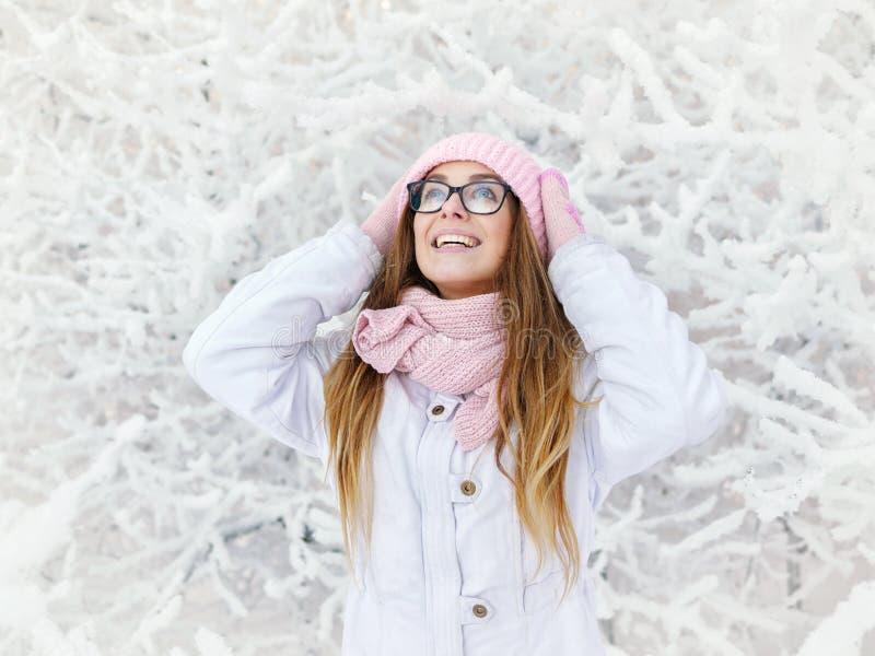 桃红色的可爱的愉快的年轻白肤金发的妇女编织了帽子围巾手套有乐趣多雪的冬天公园森林晴天本质上 免版税库存照片