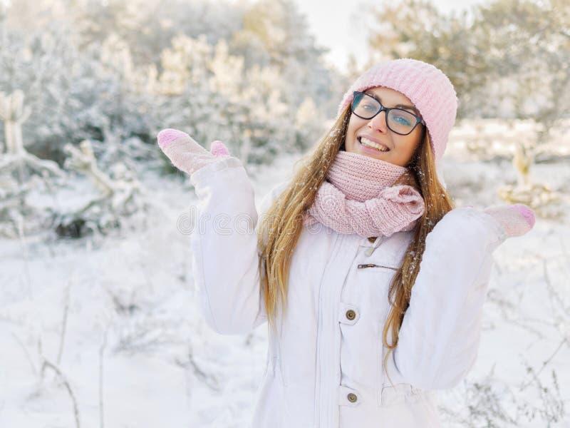 桃红色的可爱的愉快的年轻白肤金发的妇女编织了帽子围巾手套有乐趣多雪的冬天公园森林晴天本质上 库存照片