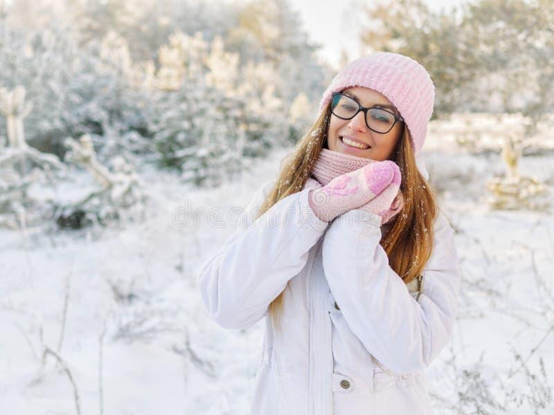 桃红色的可爱的愉快的年轻白肤金发的妇女编织了帽子围巾手套有乐趣多雪的冬天公园森林晴天本质上 库存图片