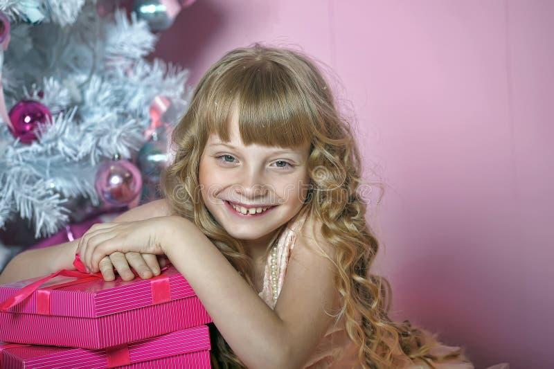 桃红色的女孩在圣诞树 免版税库存照片