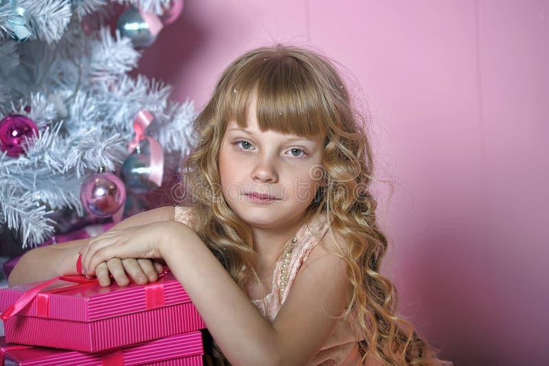 桃红色的女孩在圣诞树 库存图片