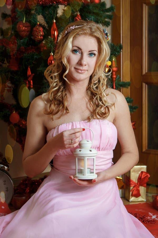 桃红色的妇女与白色点燃了灯笼在圣诞树下 库存照片