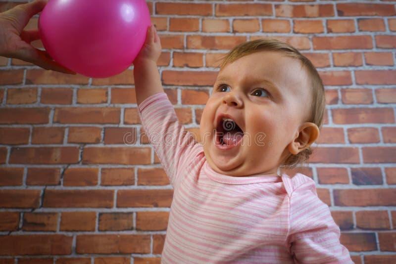 桃红色的滑稽的矮小的逗人喜爱的女婴与打篮球的球 库存照片