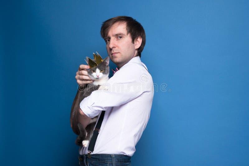 桃红色看照相机,拿着和抚摸在金黄自创冠的衬衣和黑悬挂装置的英俊的严肃的人灰色猫 免版税图库摄影
