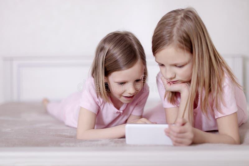 桃红色睡衣的两个女孩姐妹在床上观看智能手机和读eBook的 图库摄影
