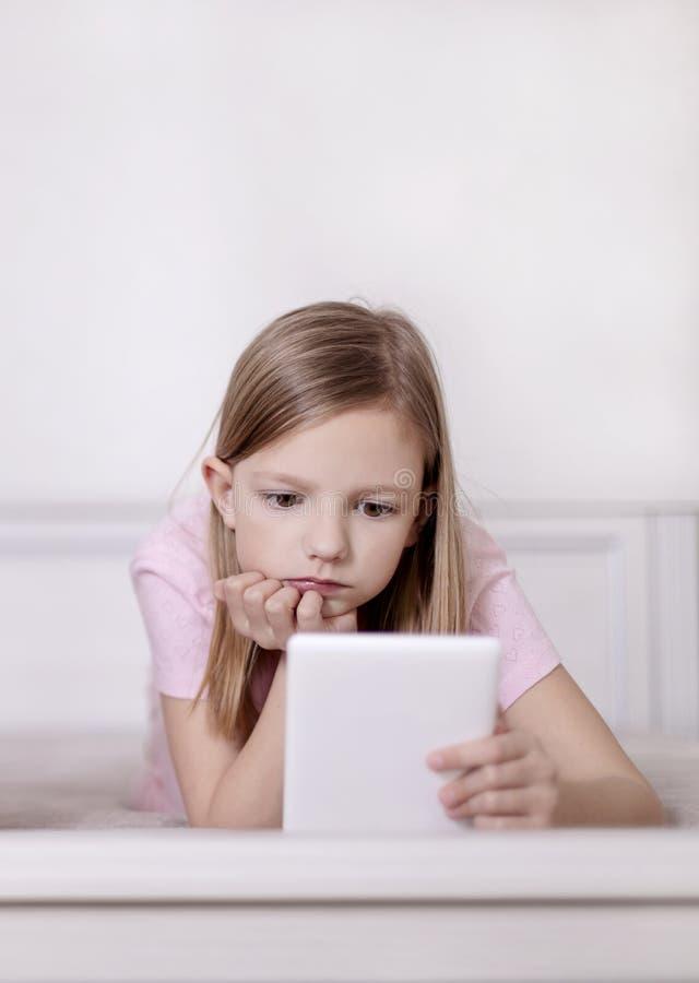 桃红色睡衣的女孩读一本电子书的在床 免版税库存图片