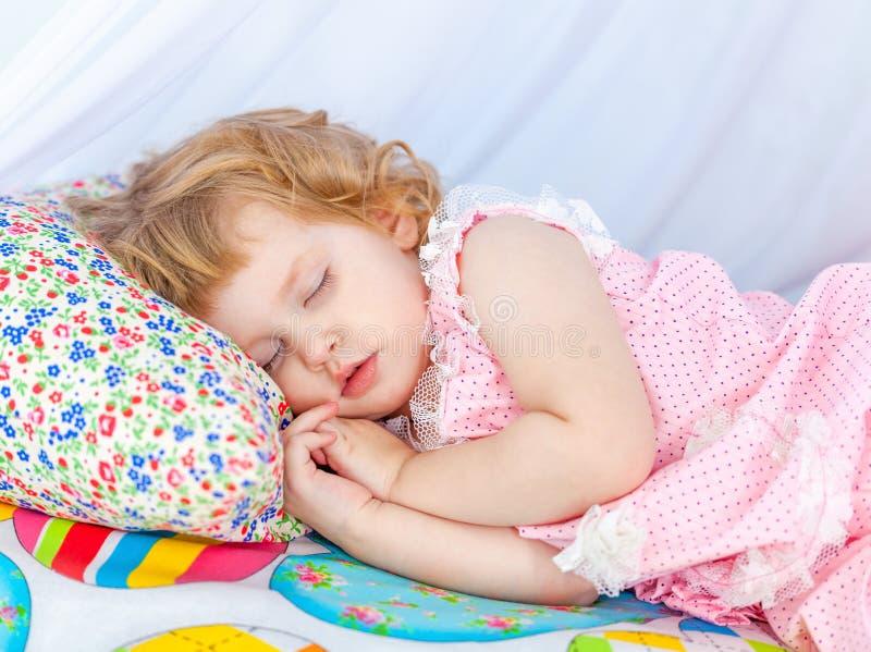 桃红色睡衣的小卷曲女孩睡觉与在一个软的轻便小床的闭合的眼睛的 免版税图库摄影