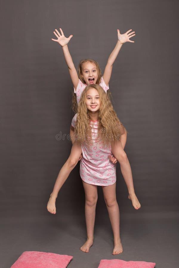 桃红色睡衣的美丽的两个女孩在上床前使用 库存照片