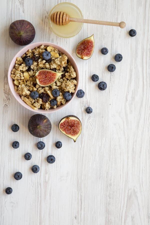 桃红色碗果子格兰诺拉麦片用果子和蜂蜜在白色木背景,顶视图 平的位置,从上面,顶上 库存图片