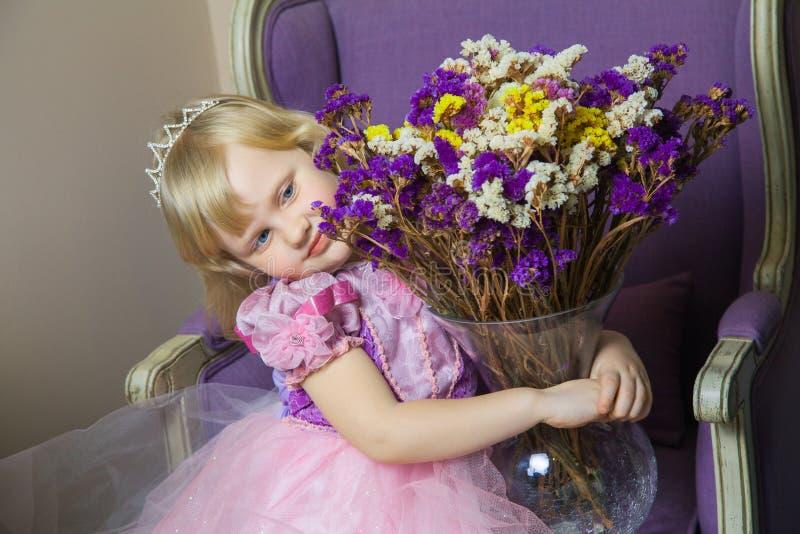 桃红色礼服和冠的小愉快的公主女孩在她的坐椅子和拿着有花的皇家室花瓶 库存照片
