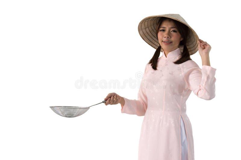 桃红色礼服和拿着炊事用具的越南帽子的妇女 免版税库存照片