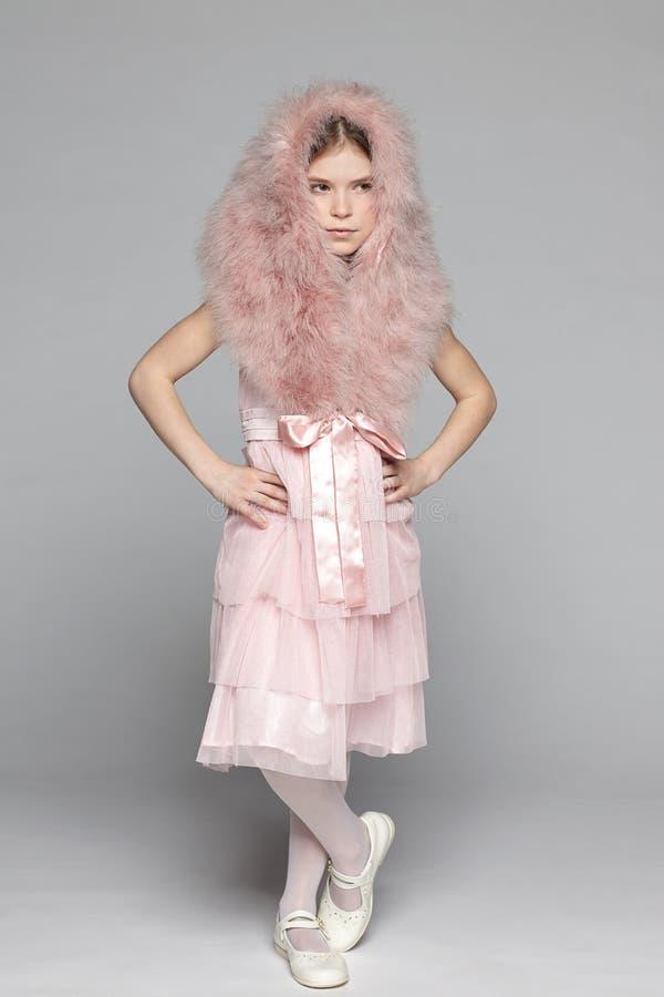 桃红色礼服和毛皮hoo的Ffashion女孩 免版税库存图片