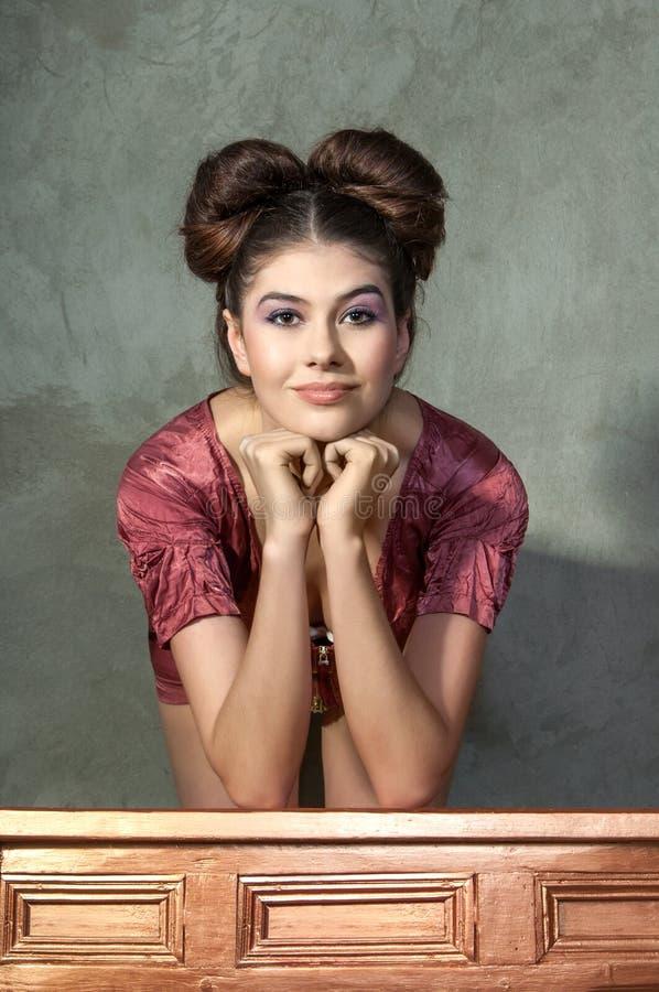 桃红色礼服和滑稽称呼的摆在的可爱的小姐  库存照片