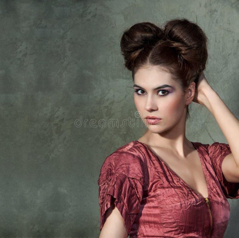 桃红色礼服和滑稽称呼的摆在的可爱的小姐  免版税库存图片