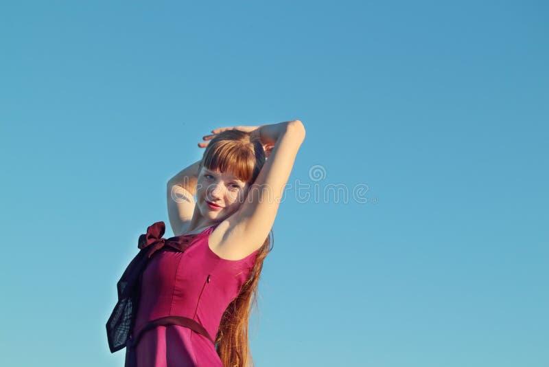 桃红色礼服摆在的美丽的少妇 图库摄影