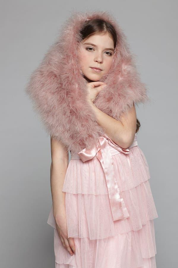 桃红色礼服和毛皮hoo的Ffashion女孩 免版税库存照片
