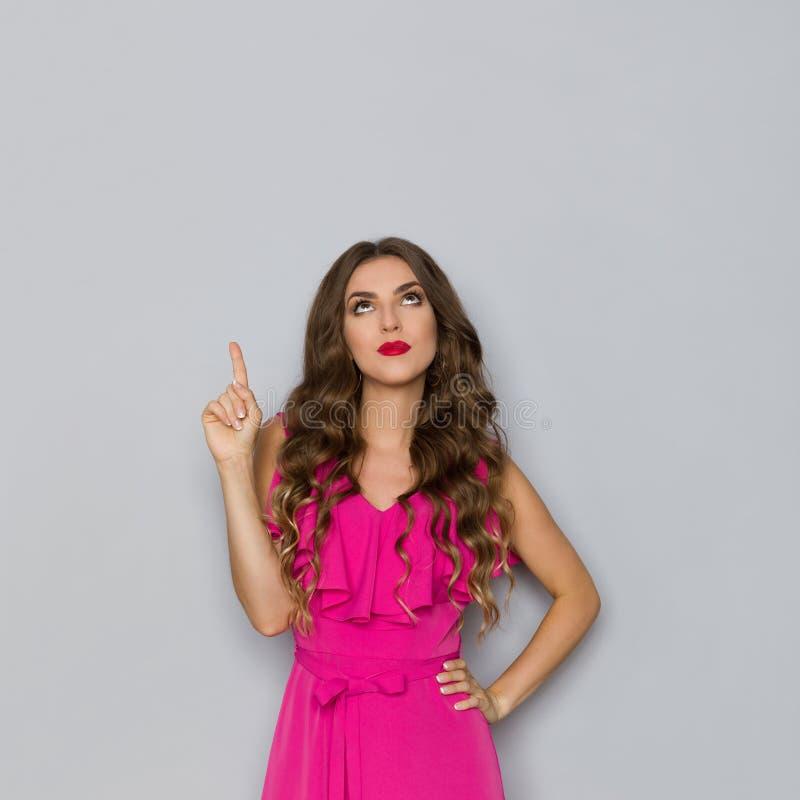 桃红色礼服的严肃的美女指向和看 库存照片