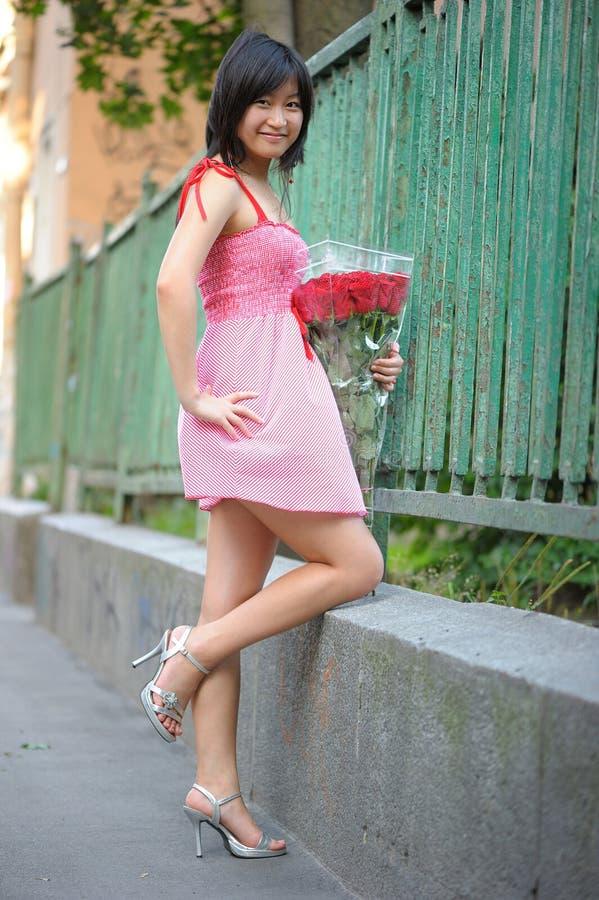 桃红色礼服的亚裔女孩有玫瑰花束的  库存图片