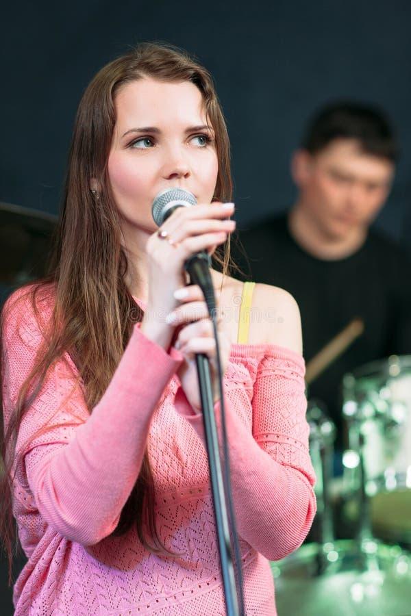 桃红色礼服的女歌手在话筒附近 免版税库存图片