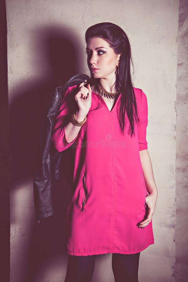 桃红色礼服的时尚妇女在墙壁 库存照片
