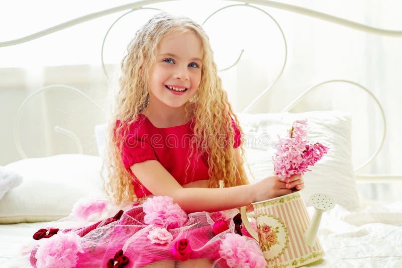 桃红色礼服的美丽的小女孩坐床 免版税库存图片