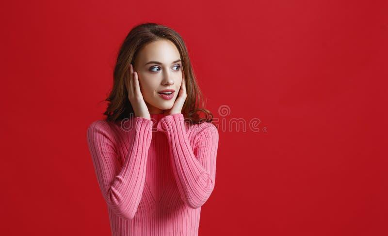 桃红色礼服的美丽的情感女孩在红色背景 免版税库存图片