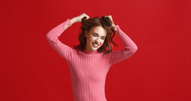 桃红色礼服的美丽的情感女孩在红色背景 图库摄影