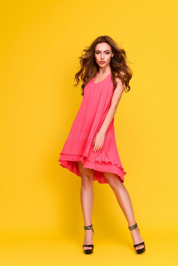 桃红色礼服的美丽的长发女孩 免版税库存图片