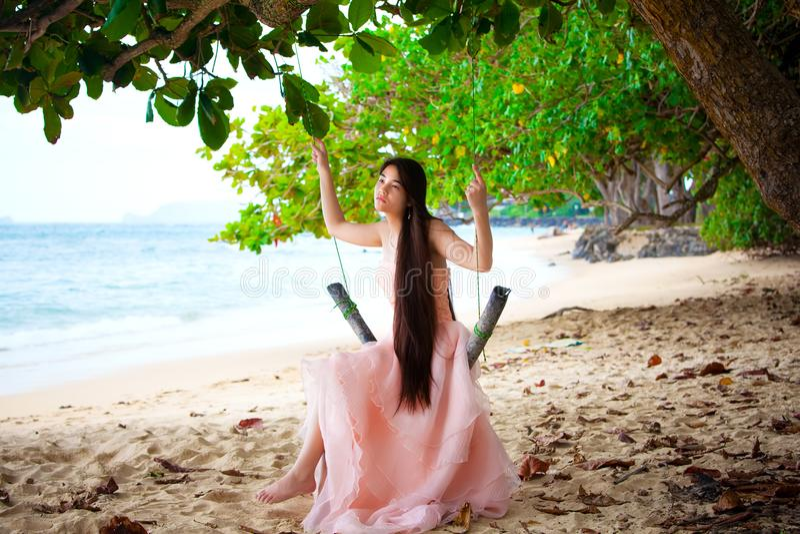 桃红色礼服的青少年的女孩坐摇摆在海滩 免版税库存照片
