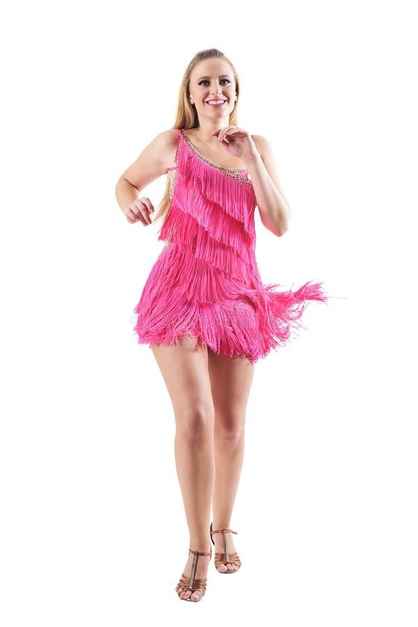 桃红色礼服跳舞的快乐的激动的妇女,微笑和看照相机 免版税库存照片