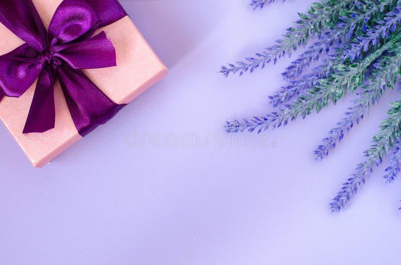 桃红色礼物盒和淡紫色在紫罗兰色背景 免版税库存照片