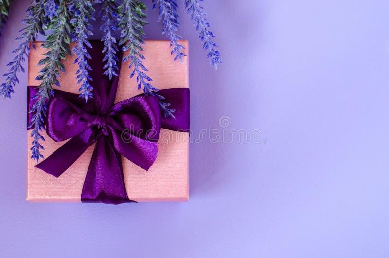 桃红色礼物盒和淡紫色在紫罗兰色背景 免版税库存图片