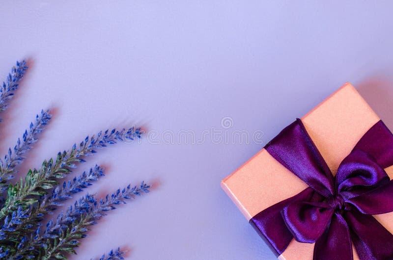 桃红色礼物盒和淡紫色在紫罗兰色背景 免版税图库摄影